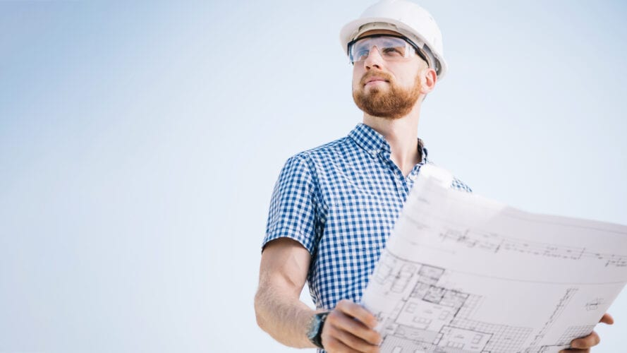 Engineer holding schematic drawing in his hands